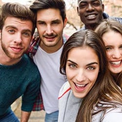 Smiling group of five young people outdoors