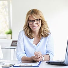 A middle-aged woman sitting at her computer screens and smiling because of her renewed confidence
