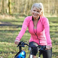 A middle-aged woman wearing a pink jacket and riding a bike smiles while enjoying her new teeth