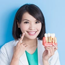 Dentist point to smile while holding model of dental implants in Dallas