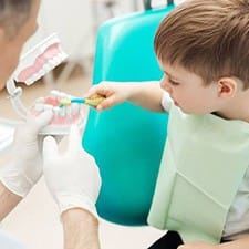 Little boy practicing tooth brushing in dental chair