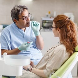 Dentist talking to female patient in dental chair