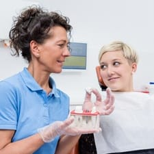 A female patient talking to a dentist about dental implants