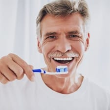 An older man brushing his teeth