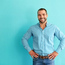 man in blue shirt smiling against blue wall
