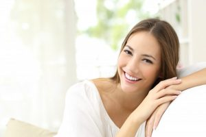A woman smiling on a couch.