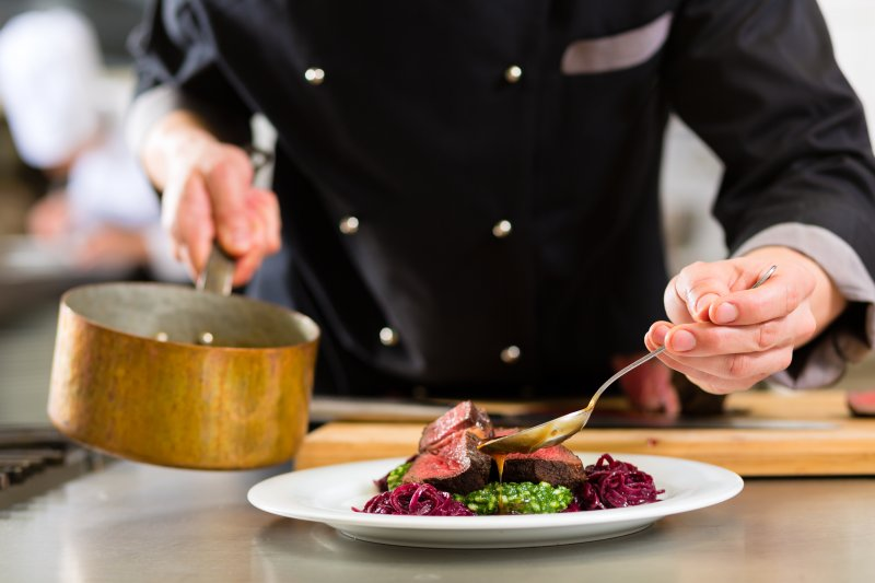 A chef pouring sauce onto a juicy steak.